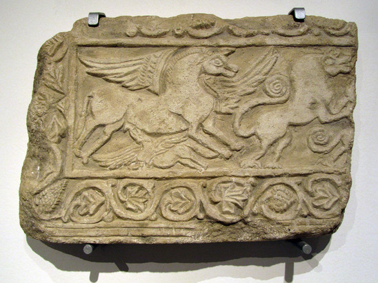 Fig. 25: Ober‐Ingelheim, Burgkirche, relief showing a winged mare, her suckling foal, a jumping lion and part of a further lion, all framed by vine tendrils (here copy at Museum bei der Kaiserpfalz Ingelheim, original at Landesmuseum Mainz). Credit: Museum bei der Kaiserpfalz Ingelheim