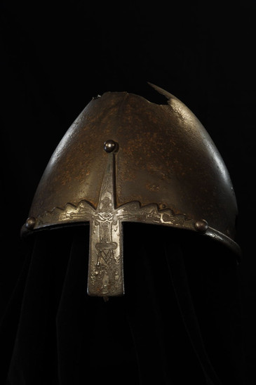 Fig. 16: Helmet, originally without the iron rim, was owned by the Přemyslids, perhaps Duke Wenceslas himself. At least since the time of Duke Boleslav II, it has been attributed to this saint and provided with a rim and 'nose guard' to commemorate the saint. Afterwards it became part of the treasury of St Vitus Cathedral and was exhibited sometimes. Prague, Metropolitan Chapter of St Vitus, treasury. Credit: Institute of Archaeology of the Academy of Sciences of the Czech Republic, Prague Castle, photo by Jan Gloc